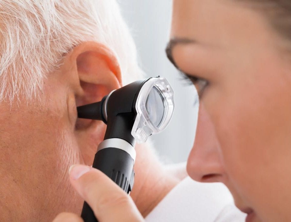 doctor-inspecting-an-older-mans-ear